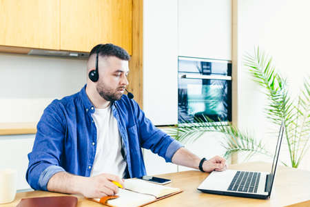 Photo pour The man uses a headset with a microphone, makes an online video call, for consultations, with the help of a laptop, works at home - image libre de droit
