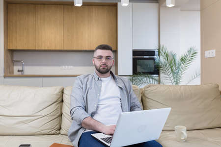 Foto de respectable handsome man working from home office, sitting on sofa with laptop, and solving business case - Imagen libre de derechos