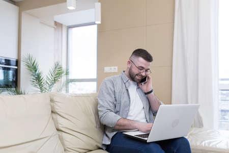Photo pour respectable handsome man working from home office, sitting on sofa with laptop, and solving business case - image libre de droit