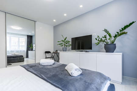 Photo pour Interior photography, bedroom, in a small studio apartment, with a large bed and white walls - image libre de droit