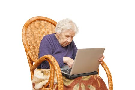 Grandmother with the laptop in an armchair