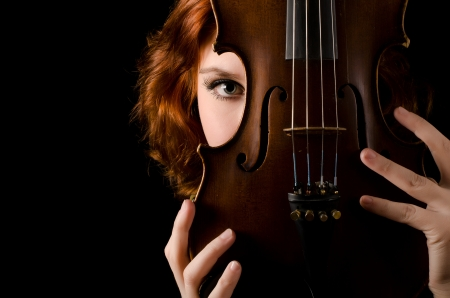 Beautiful girl with a violin on black