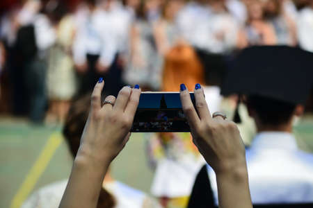 Photo for Woman using smartphone taking picture at graduation party. - Royalty Free Image