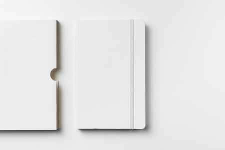 Photo pour Top view of close white notebook with elastic band and case isolated on white background - image libre de droit