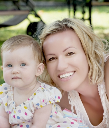 Blonde caucasian mother and baby girl looking at the camera.