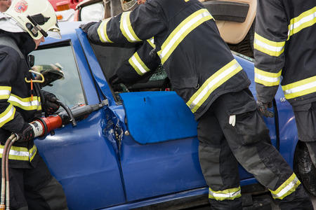 Nitra, Slovakia - September 06, 2014: Simulation of the car accident. Firemen opening the car doors with hydraulic scissors.