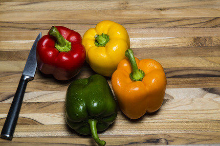 Colorful peppers on cutting board with a paring knife