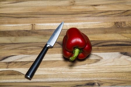 Red bell pepper and paring knife on a teak cutting board