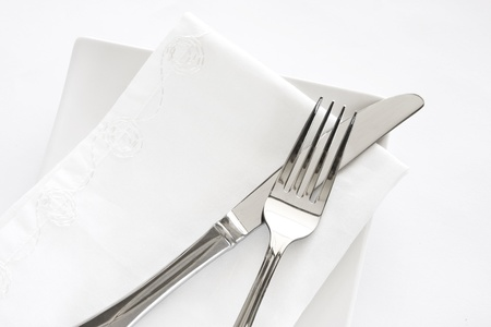 Flatware setting of a fork, knife and white napkin on a white plate against a white background.
