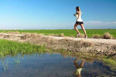 Photo for A young athlete girl in a yellow shirt running down a path between rice fields, with her reflection in the paddy water - Royalty Free Image