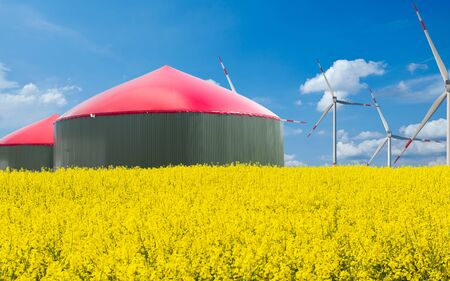 Photo for Biogas plant stands behind a arable field with blue sky - Royalty Free Image