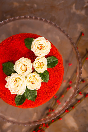 Foto de Red velvet cake decorated with white small roses with green leaves. Festive luxury cake for a birthday or wedding - Imagen libre de derechos