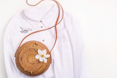 Photo for White basic shirt with stylish accessories and a wicker bag with a white flower. Top view, flat lay - Royalty Free Image