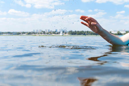 Photo pour Woman lies on SUP board and touches water with his hand and splashes - image libre de droit