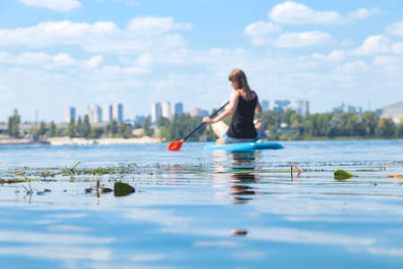 Photo for A beautiful woman is engaged in summer active sports on the river on a SUP board - Royalty Free Image