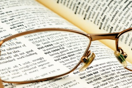 Close-up word success through glasses in open book