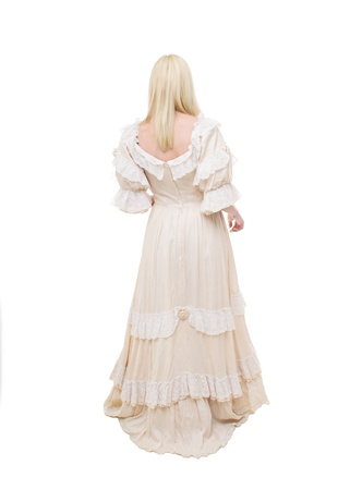 Beautiful Victorian Lady is walking in white background. View from back. Beige Dress with flowers, Ruffles and Lace. Long fair straight Hair.