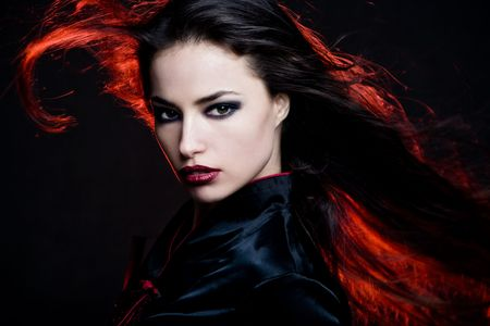 beautiful dark hair woman with hair in motion and red back light