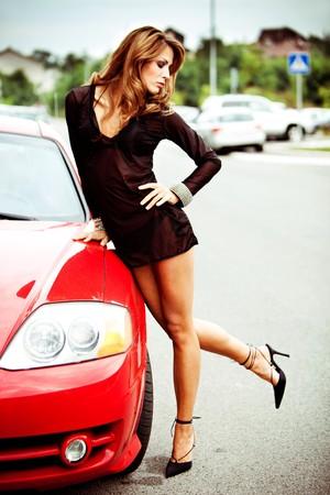 Foto de pretty woman in black transparent dress rest upon red car, outdoor shot - Imagen libre de derechos