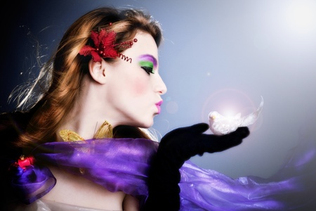 beautiful fairy sending a kiss to a little bird on her palm, profile,  studio shot