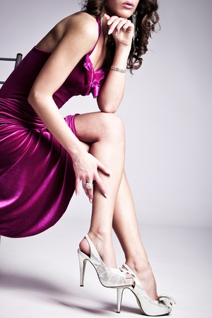 Photo for woman in purple  elegant dress and high heels sit on chair, studio shot - Royalty Free Image