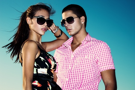 young couple with sunglasses outdoors shot against blue sky