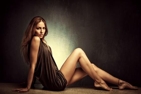 Foto de young woman in elegant short dress sit  barefoot, full body shot, studio shot - Imagen libre de derechos
