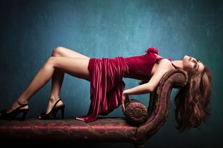 Photo pour elegant sensual young woman in red dress on recamier indoor shot - image libre de droit