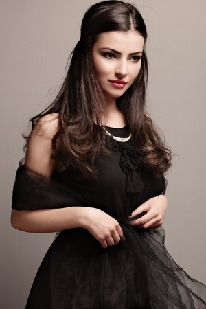 stylish elegant woman in black dress wearing pearls, studio shot