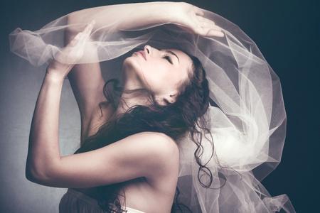 Photo pour beautiful young woman play with white veil profile studio shot - image libre de droit