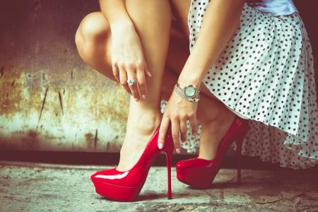 Foto de woman legs in red high heel shoes and short skirt outdoor shot against old metal door - Imagen libre de derechos
