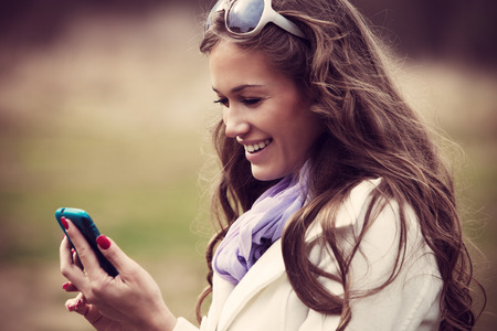 smiling young woman reading message on her smartphone outdoor shot