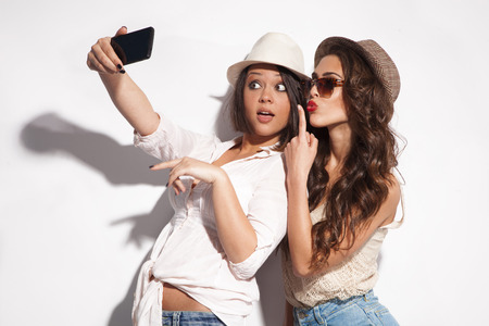 two young women taking selfie with mobile phone の写真素材