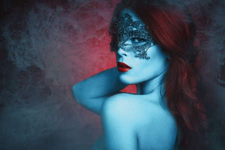 fantasy  beautiful young woman with lace mask, blue skin and red hair in haze