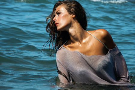 attractive young woman in blue sea water, fashion shot, hot summer day