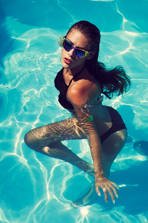 tanned young attractive woman in black bikini and sunglasses in pool