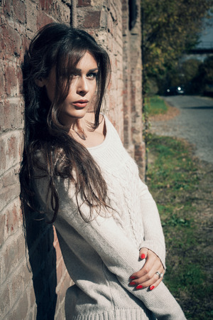 beautiful long hair young woman portrait wearing white sweater lean on red brick wall, outdor shot sunny autumn day
