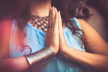 close up of woman hands in namaste gesture outdoor shot