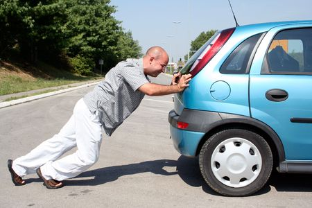 Man pushing a broken car or a car out of gas