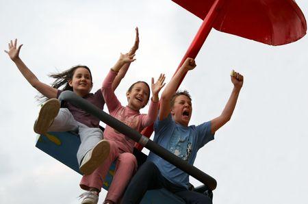 Three kids enjoying a ride on a carousel