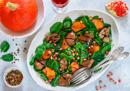 Photo pour Warm spinach salad with chicken liver, baked pumpkin and pomegranate with spices and balsamic. - image libre de droit