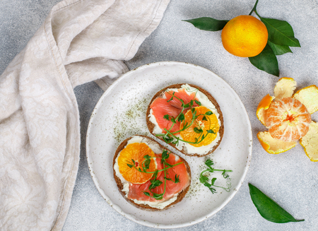 Photo pour Delicious bread toasts with cream cheese (ricotta), salted smoked salmon, tangerine and pea sprouts. Gourmet snack. Selective focus - image libre de droit