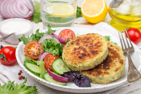 Foto de Vegetarian healthy vegetable cutlets of cabbage, potatoes, zucchini, onions and greens. Plate with lettuce, tomato and cucumber salad and patties on the table. Selective focus - Imagen libre de derechos