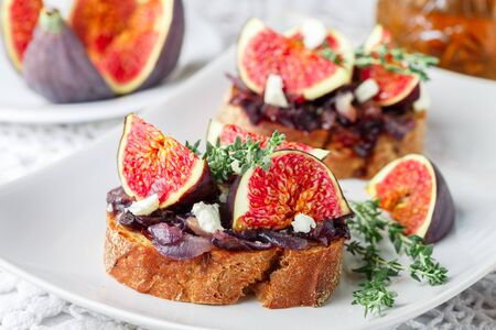 Photo pour Grain baguette sandwiches with figs, feta cheese, red onion marmalade and thyme . Delicious snack for gourmands. Selective focus - image libre de droit