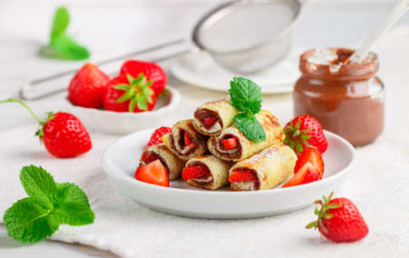 Photo pour Rolls with chocolate and nut filling, fresh strawberry berries, powdered sugar and mint. - image libre de droit