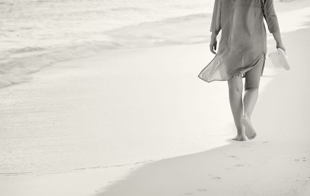 Black and white of young woman walking on the sand