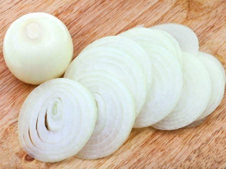 onion bulb and sliced onions on wooden cutting board close up