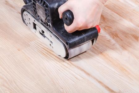 finishing ashwood surface by hand-held belt sander
