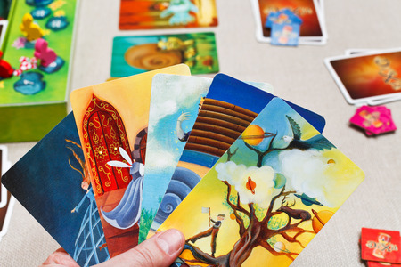 MOSCOW, RUSSIA - FEBRUARY 3, 2014: playing in Dixit card game. The game was created by Jean-Louis Roubira in 2008, and in 2010 the game received prestigious award Spiel des Jahres (Game of the Year)
