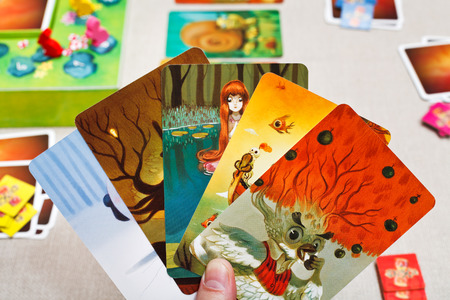 MOSCOW, RUSSIA - FEBRUARY 3, 2014: Dixit game cards in hand. The game was created by Jean-Louis Roubira in 2008, and in 2010 the game received prestigious award Spiel des Jahres (Game of the Year)